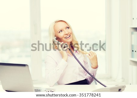 education, business, communication and technology concept - smiling businesswoman or student with laptop computer calling on phone in office - stock photo