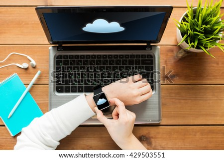 education, business, people, computing and technology concept - close up of woman with smart watch and laptop computer on wooden table with cloud icon on screens - stock photo