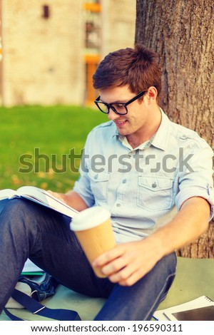 education, campus and people concept - smiling teenager in eyeglasses reading book with take away coffee