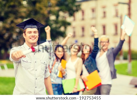 education, campus and teenage concept - smiling teenage boy in corner-cap with diploma and classmates on the back - stock photo