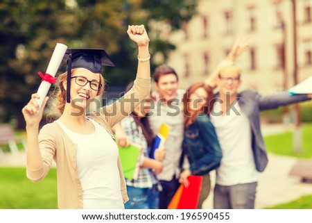 education, campus and teenage concept - smiling teenage girl in corner-cap and eyeglasses with diploma and classmates on the back - stock photo