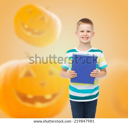 education, childhood, people and holidays concept - smiling little student boy with blue book over over halloween pumpkins background - stock photo
