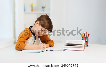 education, childhood, people, homework and school concept - smiling student boy with book writing to notebook at home - stock photo