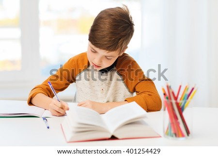 education, childhood, people, homework and school concept - student boy with book writing to notebook at home - stock photo