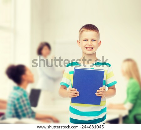 education, childhood, teamwork and school concept - smiling little student boy with blue book over group of students in classroom - stock photo