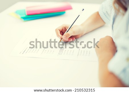 education, children and school concept - little student girl taking test - stock photo