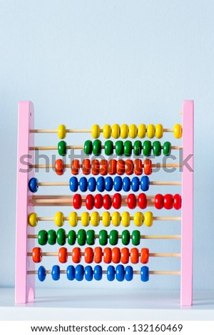 Education concept - Abacus with many colorful beads on book shelf at home - stock photo