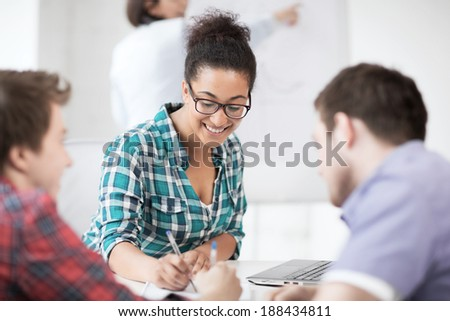 education concept - african student girl with laptop writing something in notebook