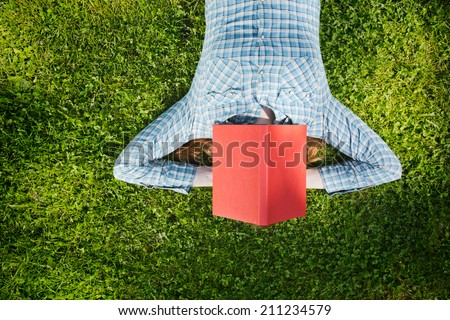 Education concept - female student lies on green grass with a red book over her head, top view. - stock photo