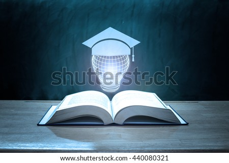 education concept,graduation cap with lamp above open book on classroom - stock photo
