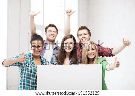 education concept - group of students at school with blank white board - stock photo