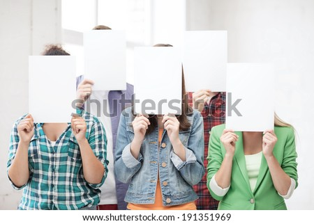education concept - group of students covering faces with blank papers - stock photo