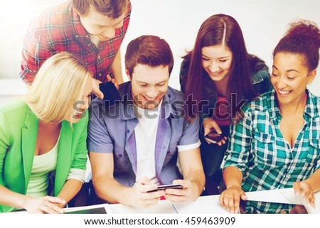 education concept - group of students looking into smartphone at school