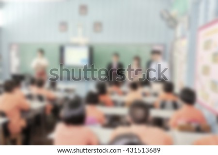 Education concept on blurred students in classroom with teachers and school director. Classroom students. Primary students. School director. Primary school kid. Free education. - stock photo