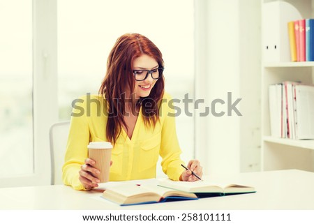 education concept - smiling student girl in eyeglasses reading books ana taking notes in library - stock photo