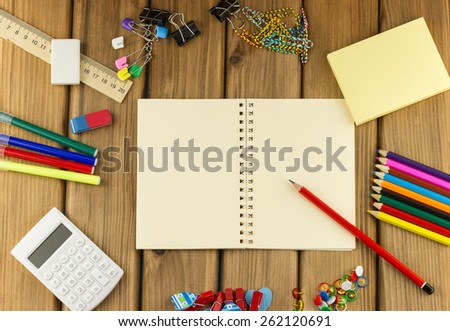 Education concept. Top view of blank notebook with school and office supplies on wooden background - stock photo
