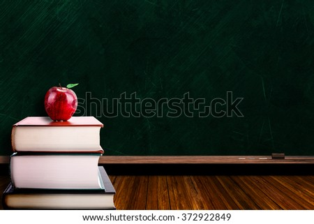 Education concept with apple on stack of books on blackboard background. Copy space on chalk board. - stock photo