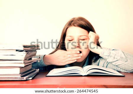 Education conceptual image. Young tired girl yawns during doing her homework. - stock photo