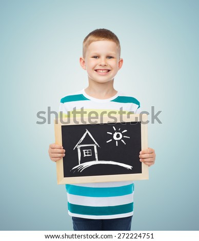 education, creativity, drawing and children concept - smiling little boy holding black chalk board with picture of home over blue background - stock photo