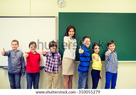 education, elementary, gesture and people concept - group of school kids and teacher showing thumbs up in classroom - stock photo