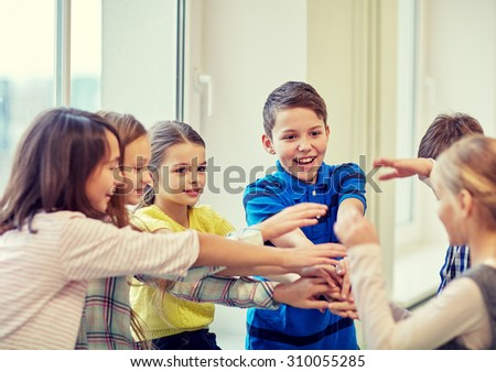 education, elementary school, children, break and people concept - group of smiling school kids putting hands on top in corridor - stock photo