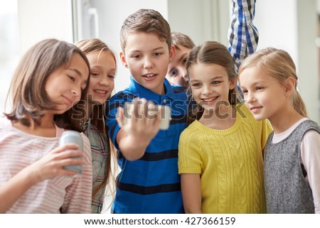education, elementary school, drinks, children and people concept - group of school kids with smartphone and soda cans taking selfie in corridor - stock photo