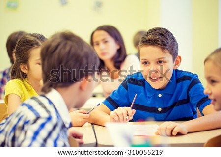 education, elementary school, learning and people concept - group of school kids talking during lesson in classroom - stock photo