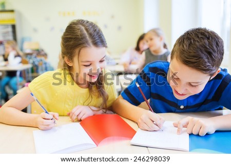education, elementary school, learning and people concept - group of school kids with pens and notebooks writing test in classroom - stock photo