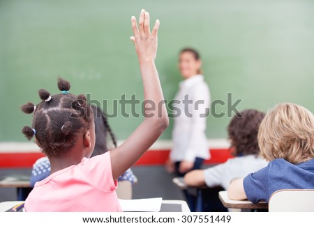 Education, elementary school, learning and people concept - group of school kids with teacher sitting in classroom and raising hand.