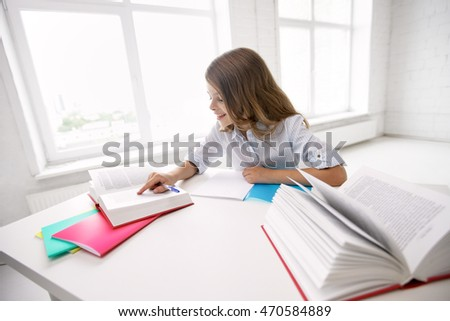 education, elementary school, learning and people concept - happy smiling girl with books and notebook doing homework