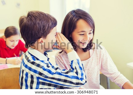 education, elementary school, learning and people concept - smiling schoolboy whispering secret to classmate ear in classroom - stock photo