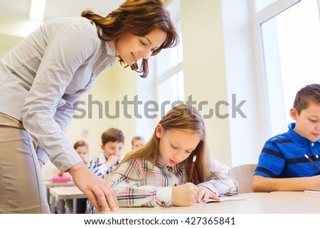 education, elementary school, learning and people concept - teacher helping school kids in classroom - stock photo