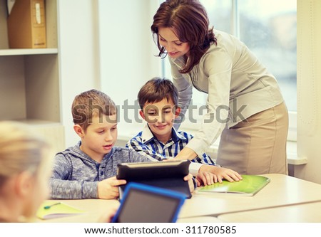 education, elementary school, learning and people concept - teacher helping school kids with tablet pc computer in classroom - stock photo