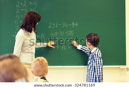 education, elementary school, learning, math and people concept - close up of little schoolboy with teacher writing on chalk board and solving task in classroom - stock photo