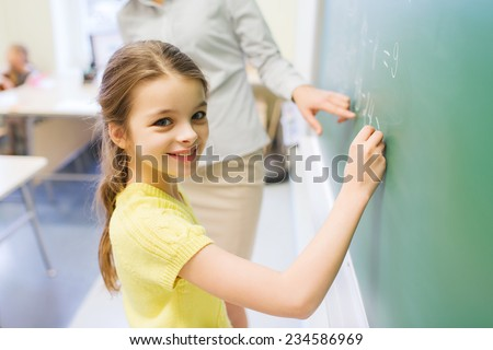 education, elementary school, learning, math and people concept - little smiling schoolgirl writing numbers on green chalk board in classroom - stock photo