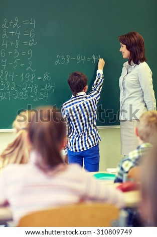 education, elementary school, learning, math and people concept - teacher and little schoolboy writing on green chalk board in classroom - stock photo