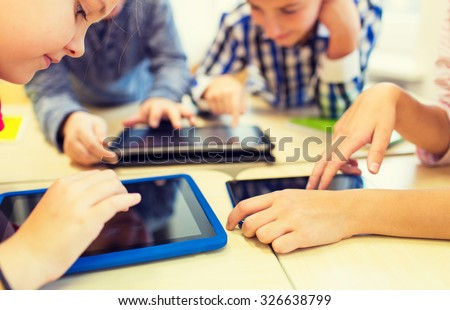 education, elementary school, learning, technology and people concept - close up of school kids with tablet pc computers having fun and playing on break in classroom - stock photo