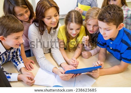 education, elementary school, learning, technology and people concept - group of school kids with teacher looking to tablet pc computer in classroom - stock photo
