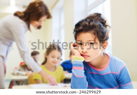 education, elementary school, people, childhood and emotions concept - sad or bored little student girl over green chalk board background - stock photo