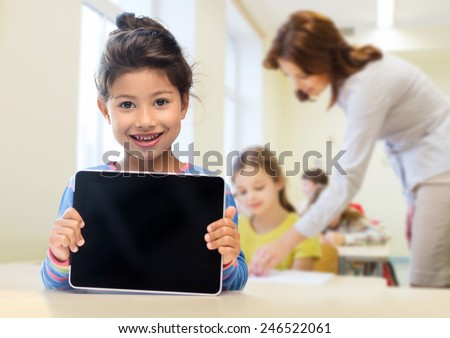 education, elementary school, technology, advertisement and children concept - little student girl showing blank black tablet pc computer screen over classroom and classmates background - stock photo
