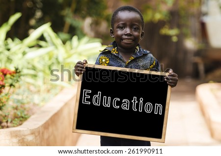 Education for Africa - African Boy Smiling with Blackboard. African male child holding a chalkboard in the streets of Bamako. - stock photo
