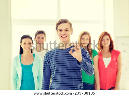 education, gesture and school concept - group of smiling students with teenage boy in front showing ok sign - stock photo