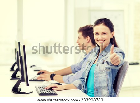 education, gesture, technology and school concept - two smiling students in computer class and girl showing thumbs up - stock photo