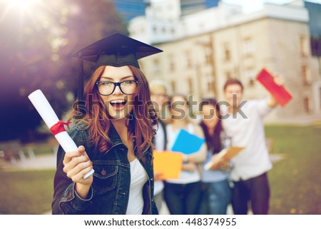 education, graduation and people concept - group of smiling students in mortarboard with diploma and school folders - stock photo