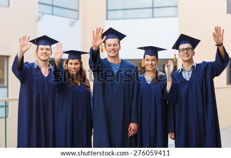 education, graduation and people concept - group of smiling students in mortarboards and gowns waving hands outdoors - stock photo