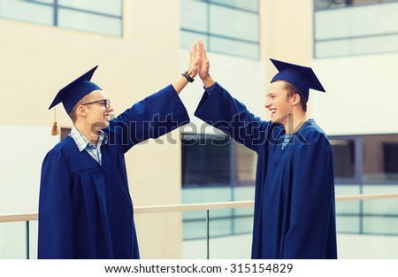 education, graduation and people concept - smiling students in mortarboards and gowns making high five gesture outdoors - stock photo