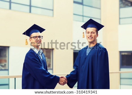 education, graduation and people concept - smiling students in mortarboards and gowns shaking hands outdoors - stock photo