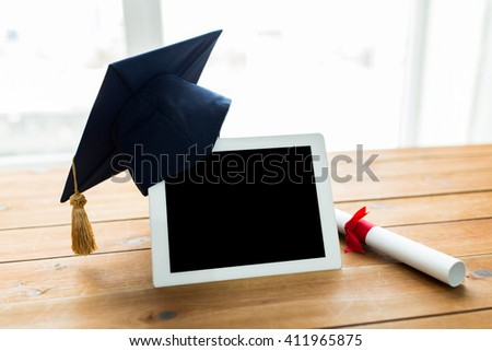 education, graduation, technology and e-learning concept - close up of tablet pc computer with mortarboard and diploma scroll on wooden table - stock photo