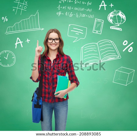 education, happiness and people concept - smiling student girl showing thumbs up over green board background - stock photo