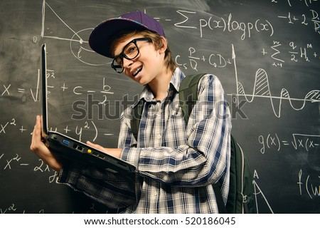 Education, high school, college. Portrait of a student boy standing by a school blackboard with his laptop.